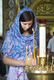 Woman lights a candle in the church Stock Image