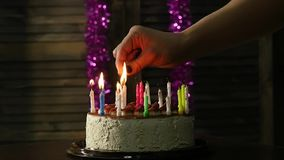 Close-up woman lights candles on tasty birthday cake. Slow motion stock video footage