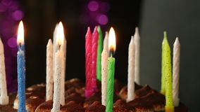 Close-up woman lights candles on tasty birthday cake. Slow motion stock video