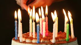 Woman lights candles on tasty birthday cake. Slow motion.  stock video
