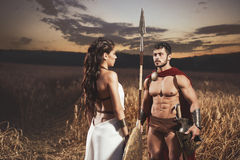 Woman like greece and man in armour meeting in field. royalty free stock photography