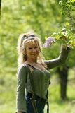 Woman with lilac. Woman smiling with a lilac tree royalty free stock photography