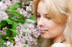 Woman with lilac flower on face Stock Photography