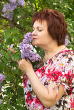 Woman and lilac. Middle-aged woman on a background of lilac bushes Royalty Free Stock Photo