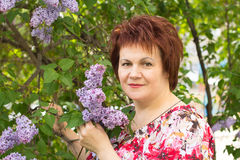 Woman and lilac. Middle-aged woman on a background of lilac bushes Royalty Free Stock Photography