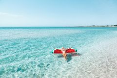 Woman on lilo on the beach. Woman on lilo in the sea water. Girl relaxing on inflatable ring on the beach. Summer vacations, idyllic scene Stock Photography
