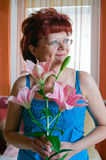 Woman and a Lily. Portrait of a smiling senior woman with lily Stock Images