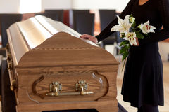 Woman with lily flowers and coffin at funeral Royalty Free Stock Photography