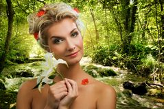 Woman with lily in forest Stock Photo