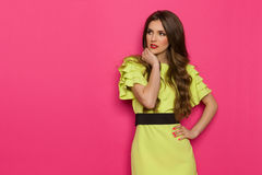 Woman In Lime Green Dress Observe. Pensive young woman in lime green dress looking away. Three quarter length studio shot on pink background Royalty Free Stock Photo