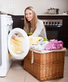 Woman with linen basket near washing machine Stock Images