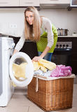 Woman with linen basket near washing machine Royalty Free Stock Images
