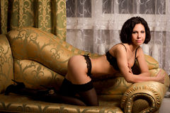Woman in lingerie on the couch Royalty Free Stock Image
