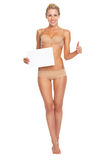 Woman in lingerie showing blank paper sheet and thumbs up Royalty Free Stock Photos