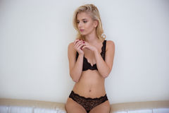 Woman in lingerie sitting on the coach Royalty Free Stock Images