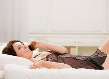 Woman in lingerie talking on cell phone in bed Royalty Free Stock Photo
