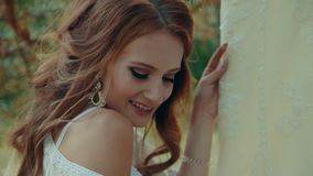 Woman in lingerie touches her wedding dress hanging on the branch of a pine. stock video footage