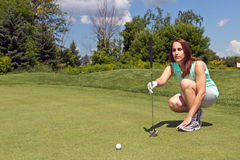 Woman lining up her putt on the golf green stock photography