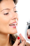 Woman and lipgloss. A picture of a beautiful girl putting on lipgloss over white background Royalty Free Stock Image