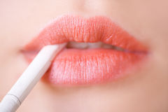 Woman lips with a cigarette. Woman rose lips holding a white cigarette Stock Image