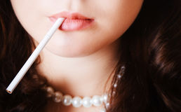 Woman lips holding a cigarette. Woman lips holding a thin white cigarette Royalty Free Stock Photos