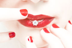Woman lips wedding ring. Woman holding wedding ring between her red lips Royalty Free Stock Photos