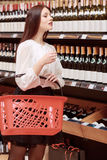Woman in a liquor store. Best choice of wine. Beautiful brunette woman holding a shopping basket chooses wine in liquor store Stock Photos