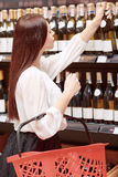 Woman in a liquor store Royalty Free Stock Image