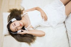 Woman listen music in house by top view. Flat lay or top view portrait of Happy beautiful Asian woman sleep and listen music on white sheet and pillow in bedroom Royalty Free Stock Photo