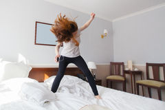 Woman listen to rock music and head bang on bed Royalty Free Stock Photos
