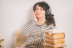 Woman listening an audiobook. On smartphone sitting between piles of paper books on the floor Stock Image