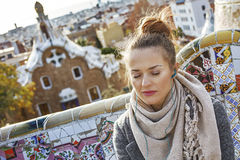 Woman listening audioguide while sitting on bench in Barcelona. Barcelona signature style. relaxed modern traveller woman in coat at Guell Park in Barcelona Stock Image