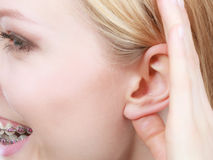 Woman listening carefully with hand close to ear Stock Photo