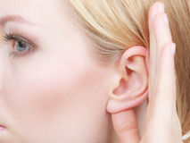 Woman listening carefully with hand close to ear. Rumors, gossip and gestures concept. Blonde woman listening carefully with hand close to ear stock images