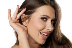 Woman listening carefully. Smiling young woman listening carefully with her hand behind her ear stock images