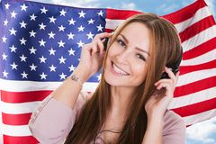 Woman Listening English Language Audiobook. Woman Listening English Language Learning Course Audiobook In Front Of American Flag Royalty Free Stock Image