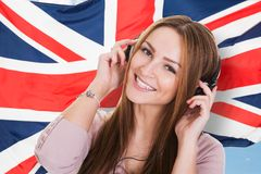 Woman listening english language audiobook. Woman Listening Language Learning Course Audiobook In Front Of British Flag Royalty Free Stock Image