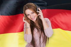 Woman listening german learning audiobook. In Front Of German Flag Royalty Free Stock Photo