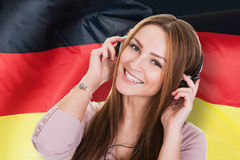 Woman Listening German Learning Audiobook. In Front Of German Flag Stock Photo
