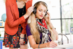 Woman listening in headphones with her colleague Stock Photos