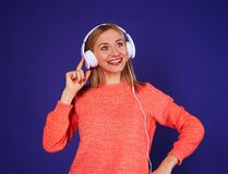 Woman listening interesting podcast. Studio shot Royalty Free Stock Image