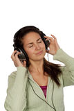 Woman listening music. Over white background wearing green t-shirt Stock Photography