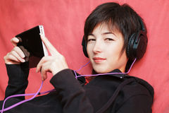 Woman listening music. Woman lying with digital tablet Royalty Free Stock Photo