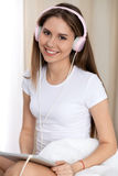 Woman listening music in bed with pink headphones after wake up, entering a day happy and relaxed after good night sleep Stock Photography