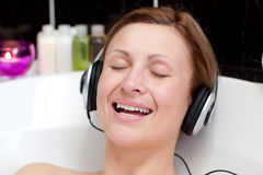 Woman listening music  in a bubble bath Stock Photo