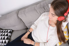 Woman listening music on couch. Stock Images