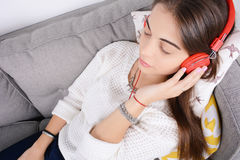 Woman listening music on couch. Royalty Free Stock Image