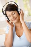 Woman listening music on headphones Stock Photo