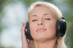 Woman listening music in headphones Royalty Free Stock Photos