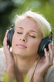 Woman listening music in headphones Stock Image